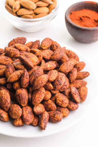 A plate holds a pile of bacon-flavored almonds. There is a bowl of raw almonds and a bowl with spices in the background.