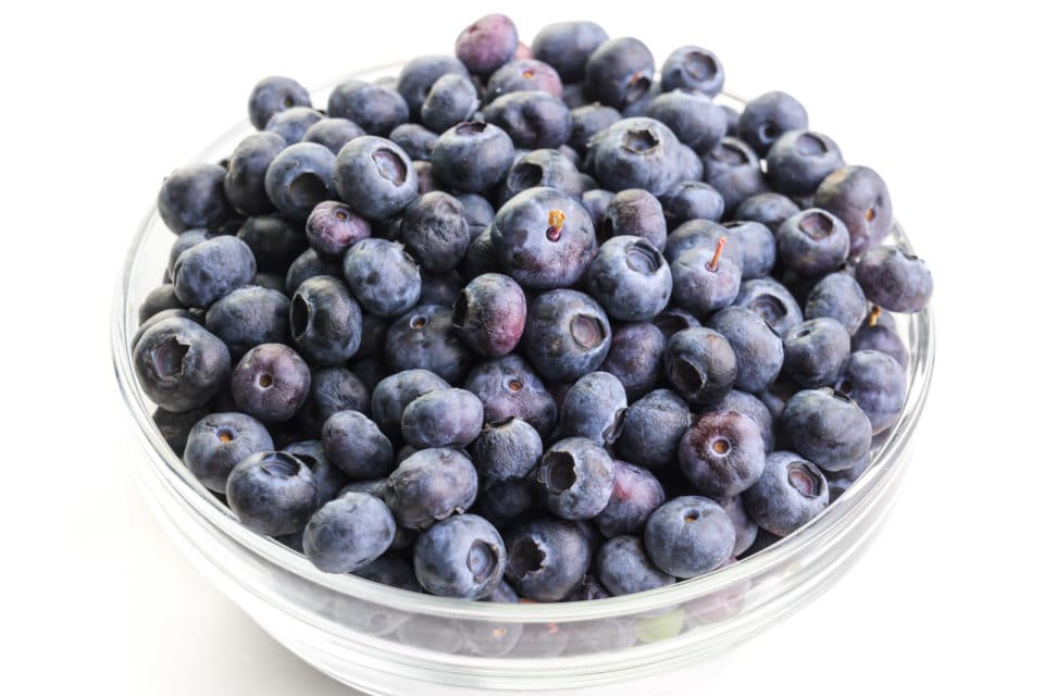 A glass bowl holds fresh blueberries.
