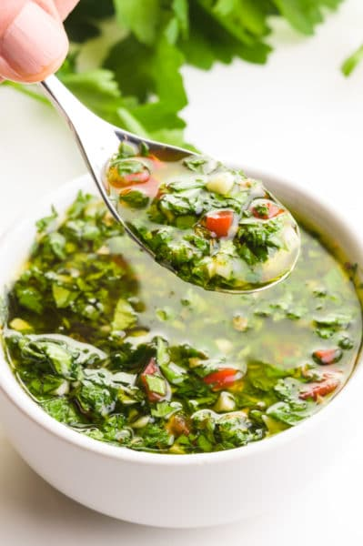 A hand holds a spoonful of chimichurri sauce, hovering over a bowl full of it. There are fresh green herbs in the background.