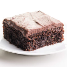 A piece of chocolate zucchini cake sits on a plate. It has frosting on top.