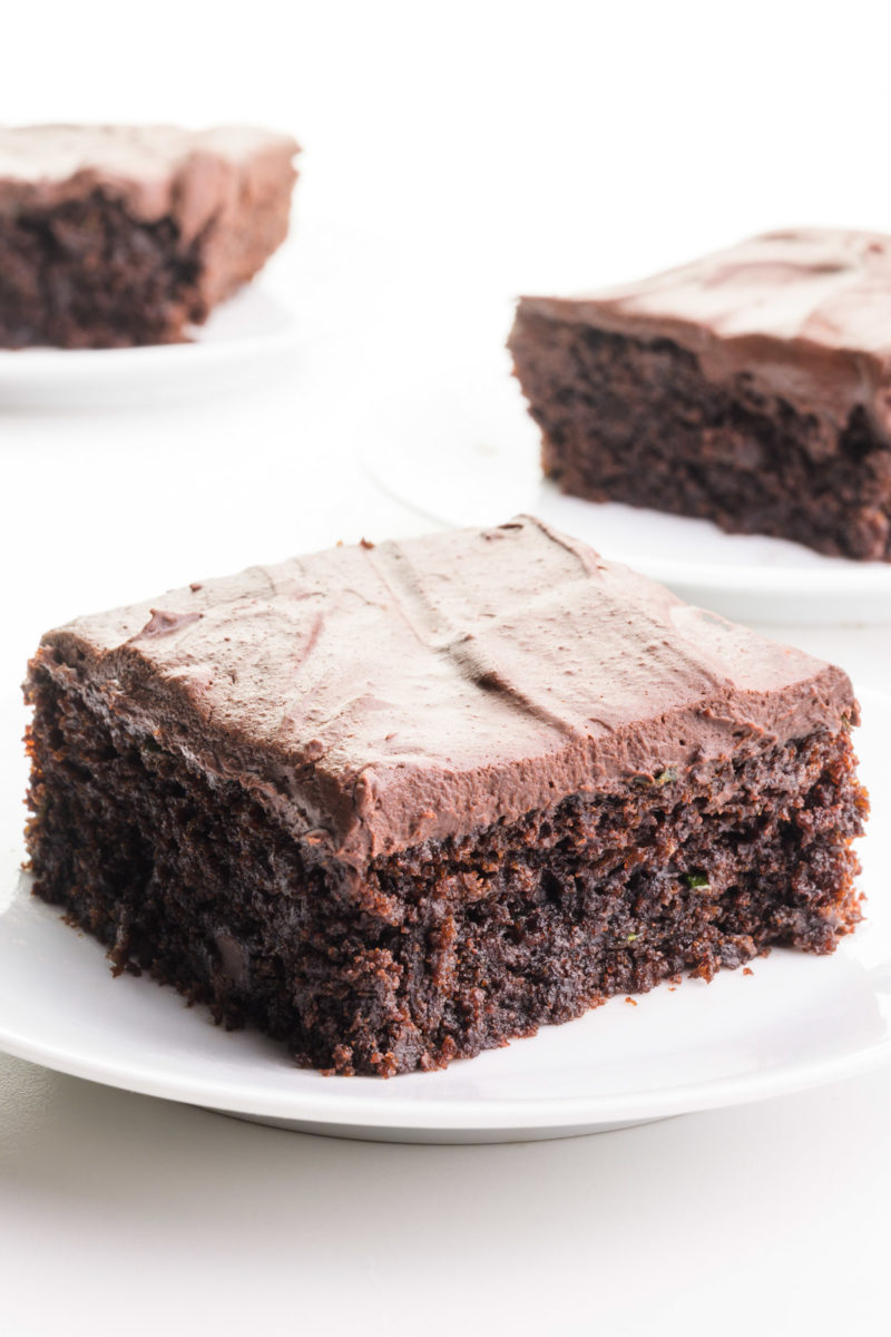 Three slices of vegan chocolate zucchini cake are on plates. They all are topped with chocolate frosting.
