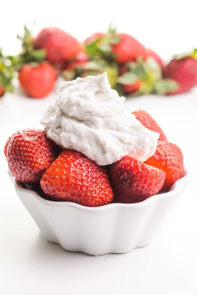 A bowl of strawberries has coconut whipped cream on top. There are more strawberries in the background.