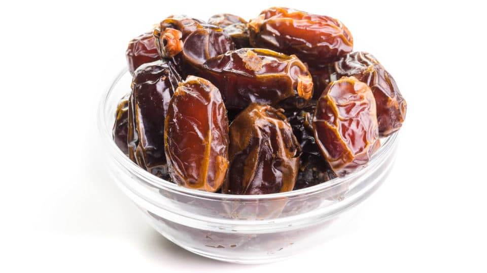 A mound of Medjool dates sit in a glass bowl on a white counter.