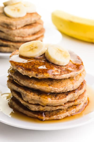 A plate holds several gluten-free banana pancakes with syrup on top. There are sliced bananas on top of the stack. There's another stack of pancakes on a plate next to a banana in the background.