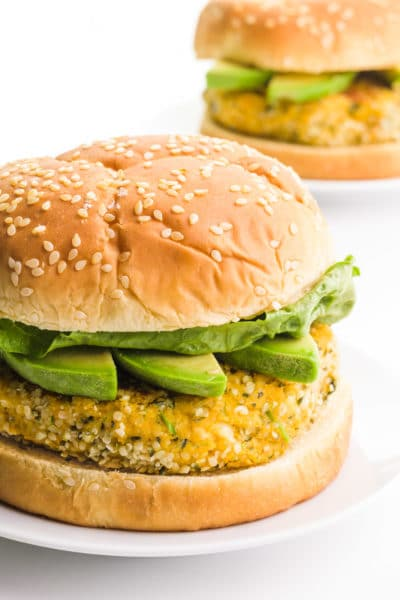 A hemp burger sits on a plate. It has avocado slices and lettuce on it. There's another one on a plate behind it.