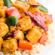A dish of kung pao tofu is served over rice. There is a bowl with more rice in the background.