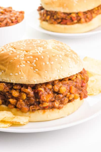 Two buns sit on plates. There is a lentil sloppy Joe mixture in the buns. There are potato chips next to the front plate and a bowl with more lentil mixture by the back plate.