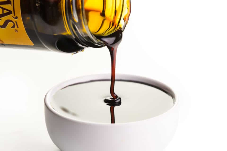 A jar of molasses is pouring into a small white bowl