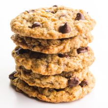A stack of vegan oatmeal chocolate chip cookies sits on a white counter.