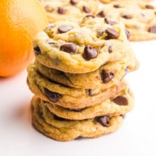 Orange chocolate chip cookies are stacked in front of an orange and more cookies in he background.