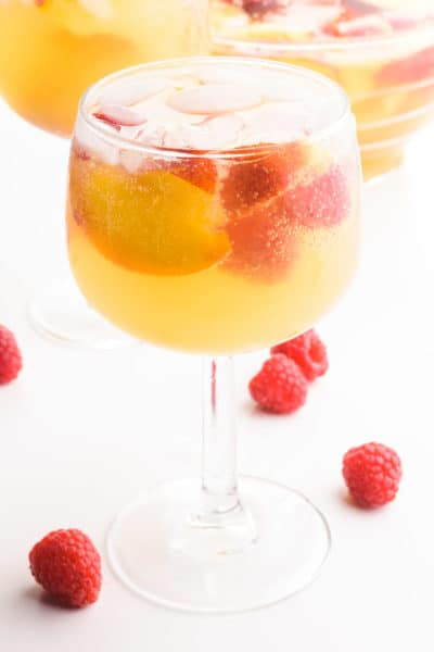 A wine glass holds peach sangria, ice cubes, raspberries, and peach slices. There is another glass and a pitcher in the background. There are fresh raspberries on the table beside the glasses.