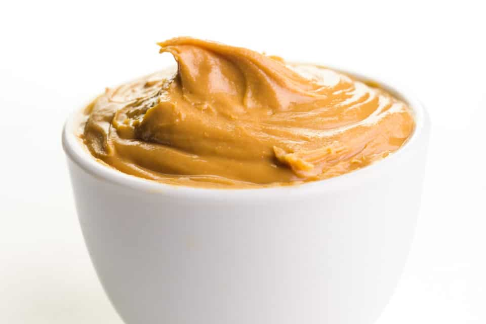 A small, white bowl holds creamy peanut butter inside.
