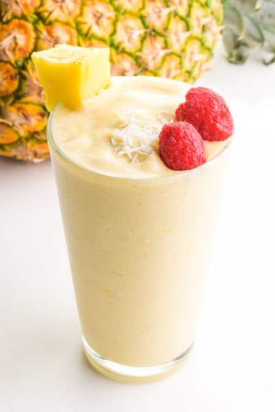 A glass full of Pina colada smoothie has raspberries, coconut flakes, and a pineapple chunk on top. It sits in front of a pineapple.
