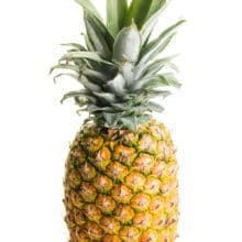 A whole pineapple sits on a white counter.