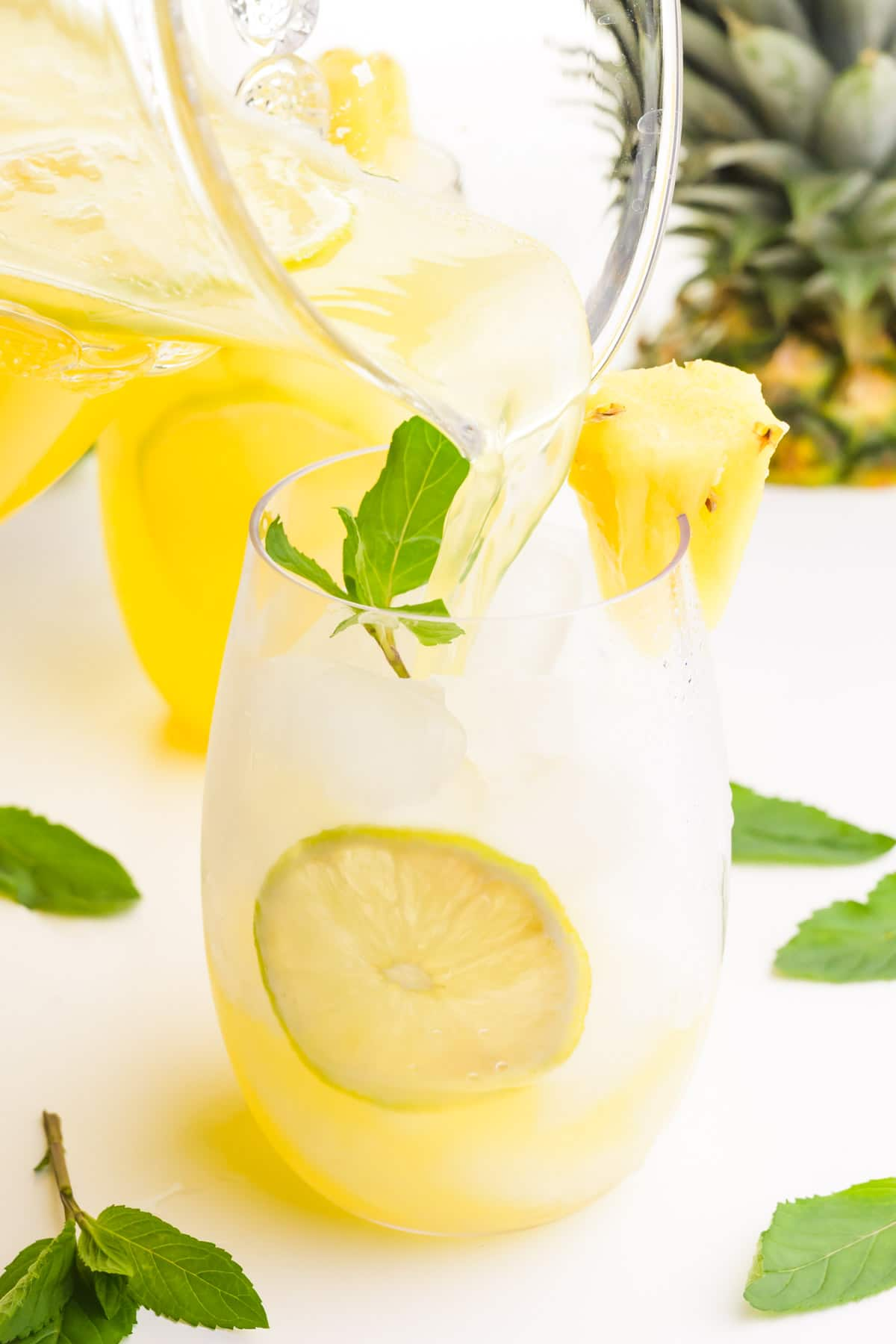 A pitcher is pouring pineapple beverage into a glass of ice with lime slices. There is a mint sprig and pineapple chunk on the glass. There are mint sprigs around the glass and the top of a fresh pineapple in the background.