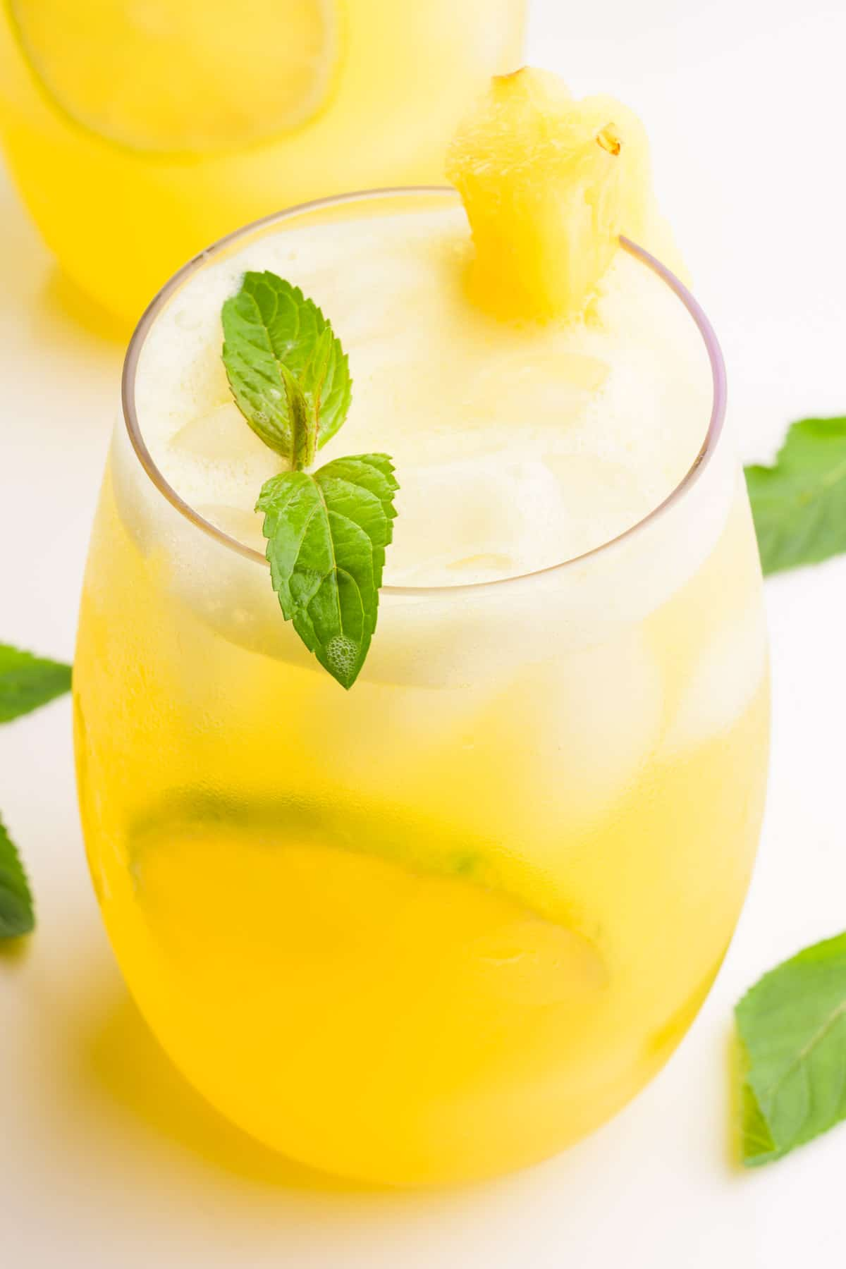 A glass holds pineapple agua Fresca with ice cubes and lime slices. There are mint sprigs in the glass and around it. There's another glass in the background.