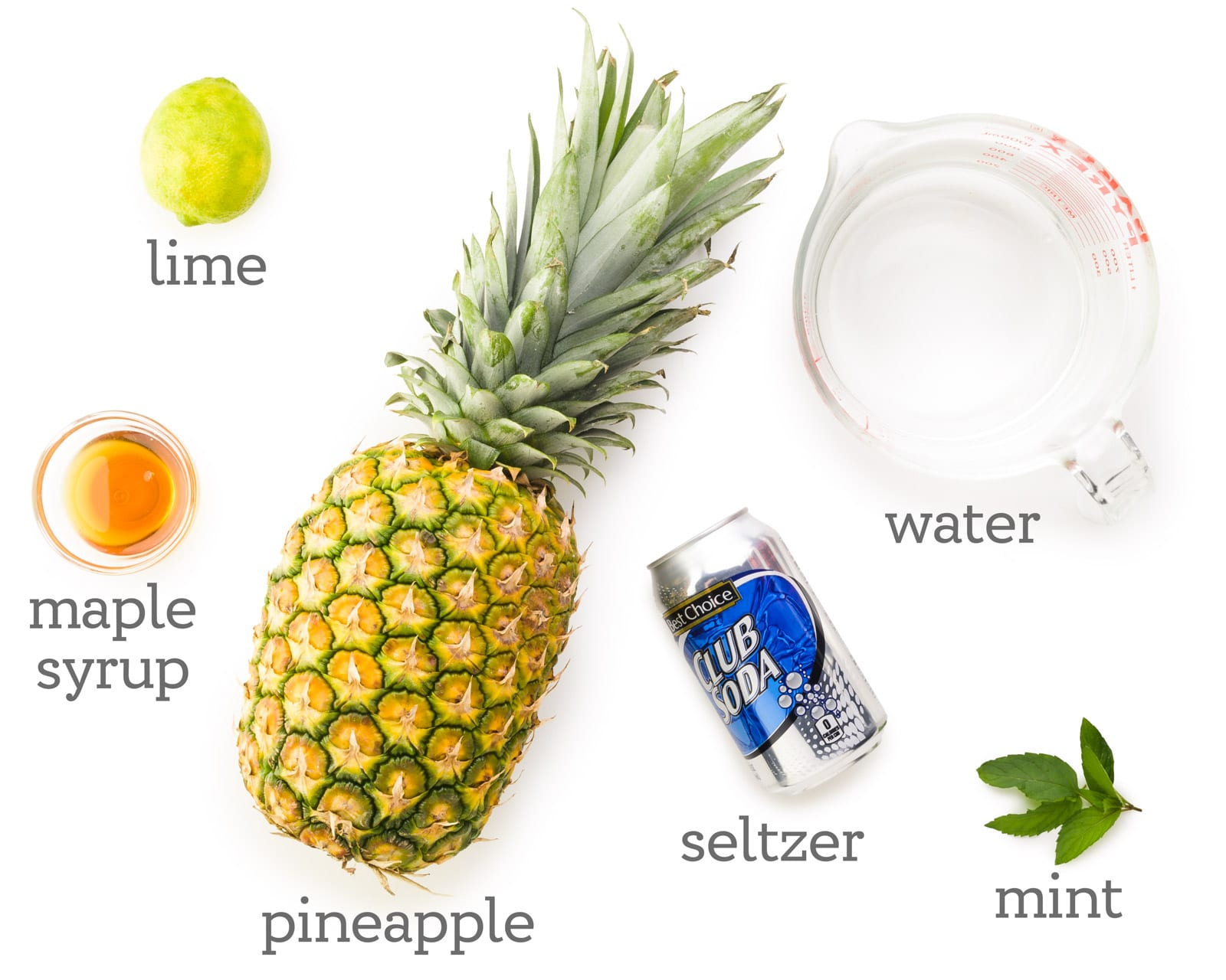 Ingredients are laid out on a white table. The labels next to them read, water, mint, seltzer, pineapple, maple syrup, and lime.