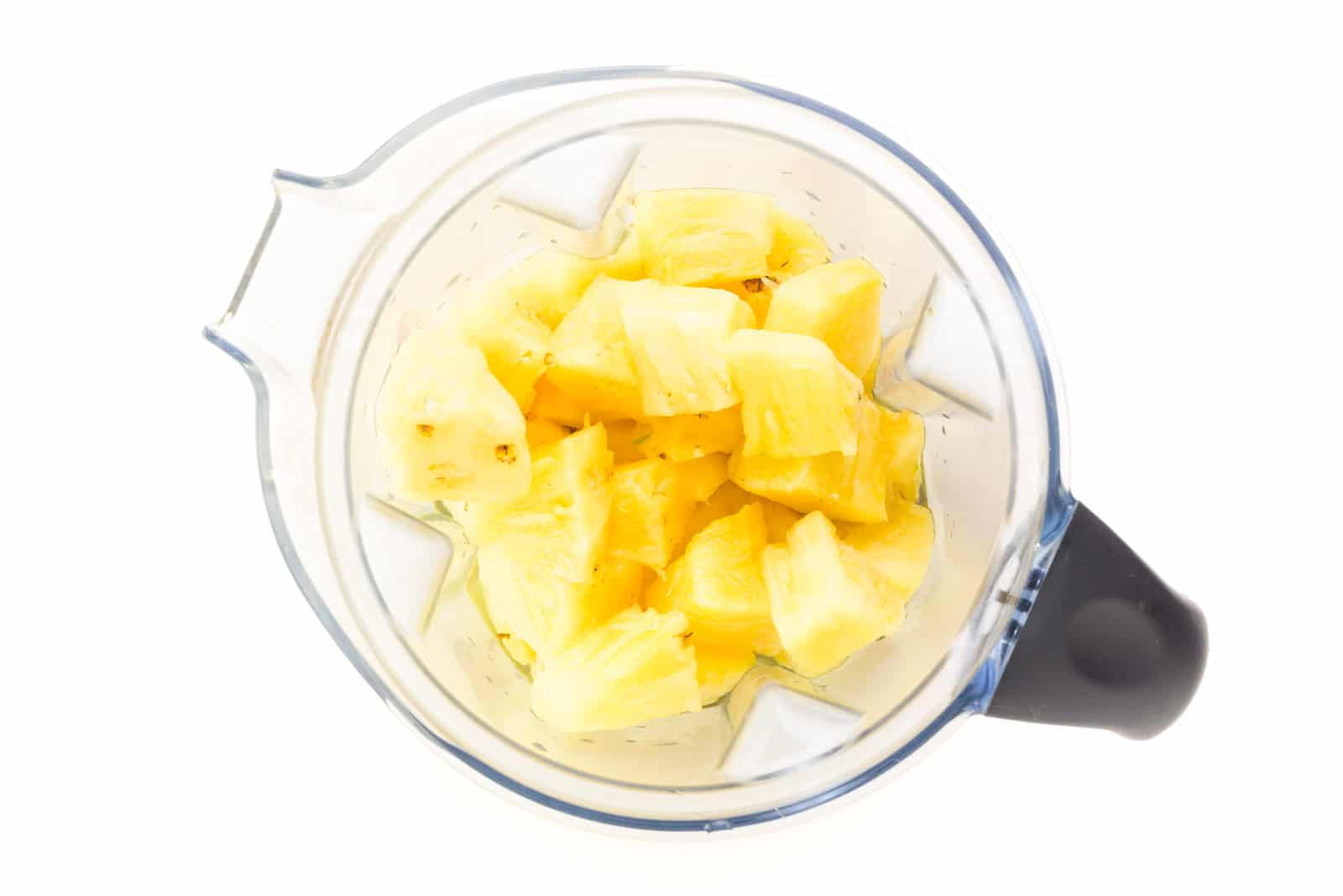 Looking down on pineapple chunks in a blender.