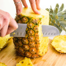 The top and bottom of a fresh pineapple have been chopped off. A hand holds a knife, cutting down the outer edge of the pineapple to remove the outer layer.