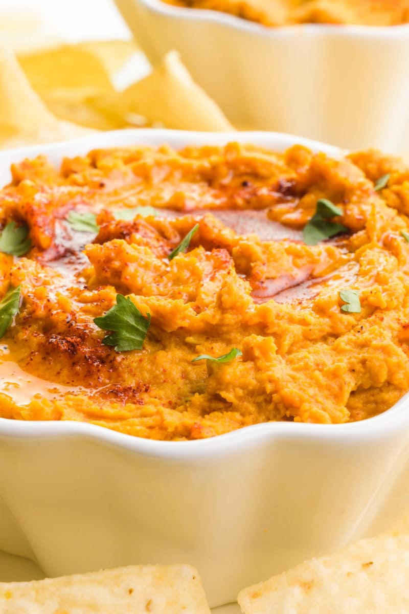 A close-up shot of sweet potato hummus in a bowl. It's topped with chopped cilantro, olive oil, and paprika. There's another bowl and tortilla chips in the background.
