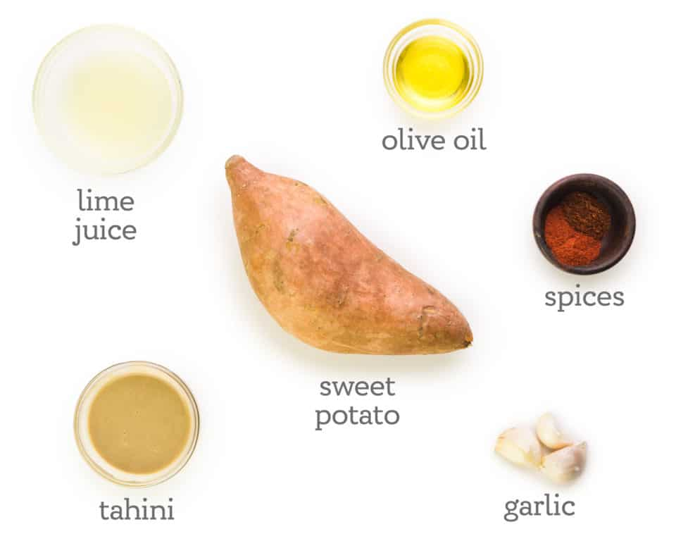 Ingredients are sitting on a white table. The labels next to them read, olive oil, spices, garlic, sweet potato, tahini, and lime juice.