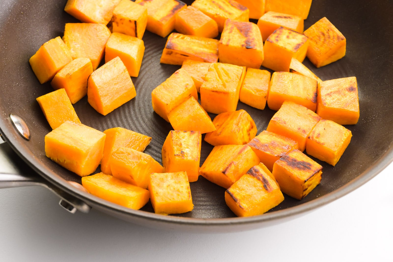 Sweet potato cubes are being sautéed in a skillet.