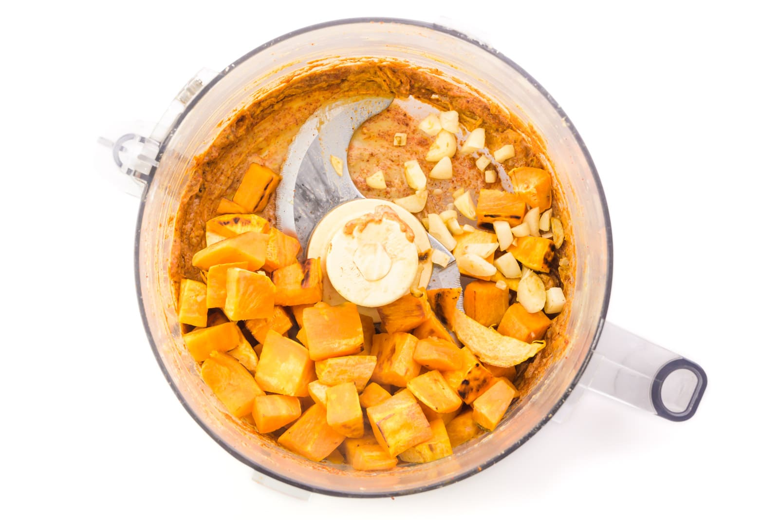 Ingredients are in a food processor, such as sweet potatoes, garlic, and other ground up ingredients.