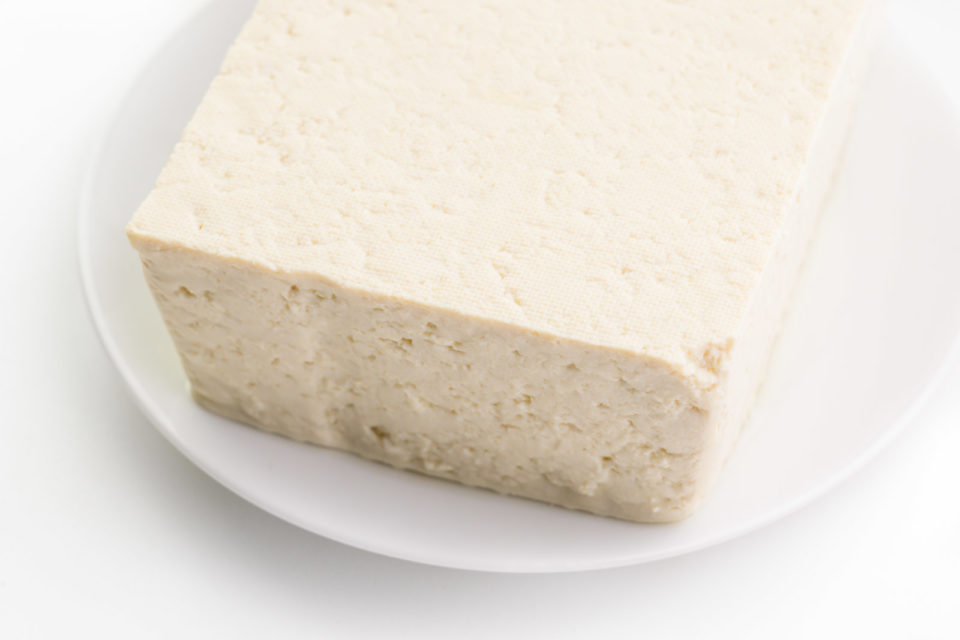 A block of extra firm tofu sits on a white plate.