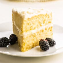 A slice of two-layer vegan vanilla cake with blackberries sitting next to it