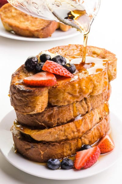 Syrup is being poured over a stack of vegan French toast. There's a plate with more French toast in the background.