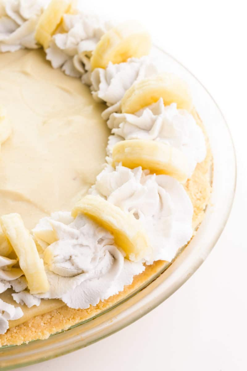 Looking down on the edge of a banana cream pie with decorative coconut cream and banana slices on top.