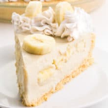 A slice of vegan banana cream pie sits on a plate. It has sliced bananas and coconut whipped cream on top.