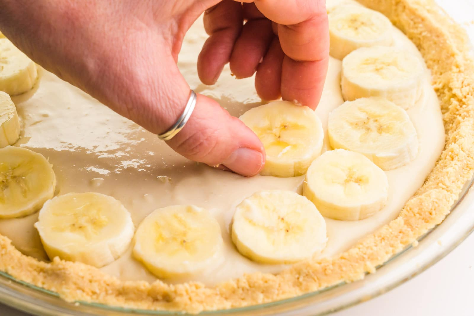 A hand is placing sliced bananas on a pie filled with vanilla pudding.