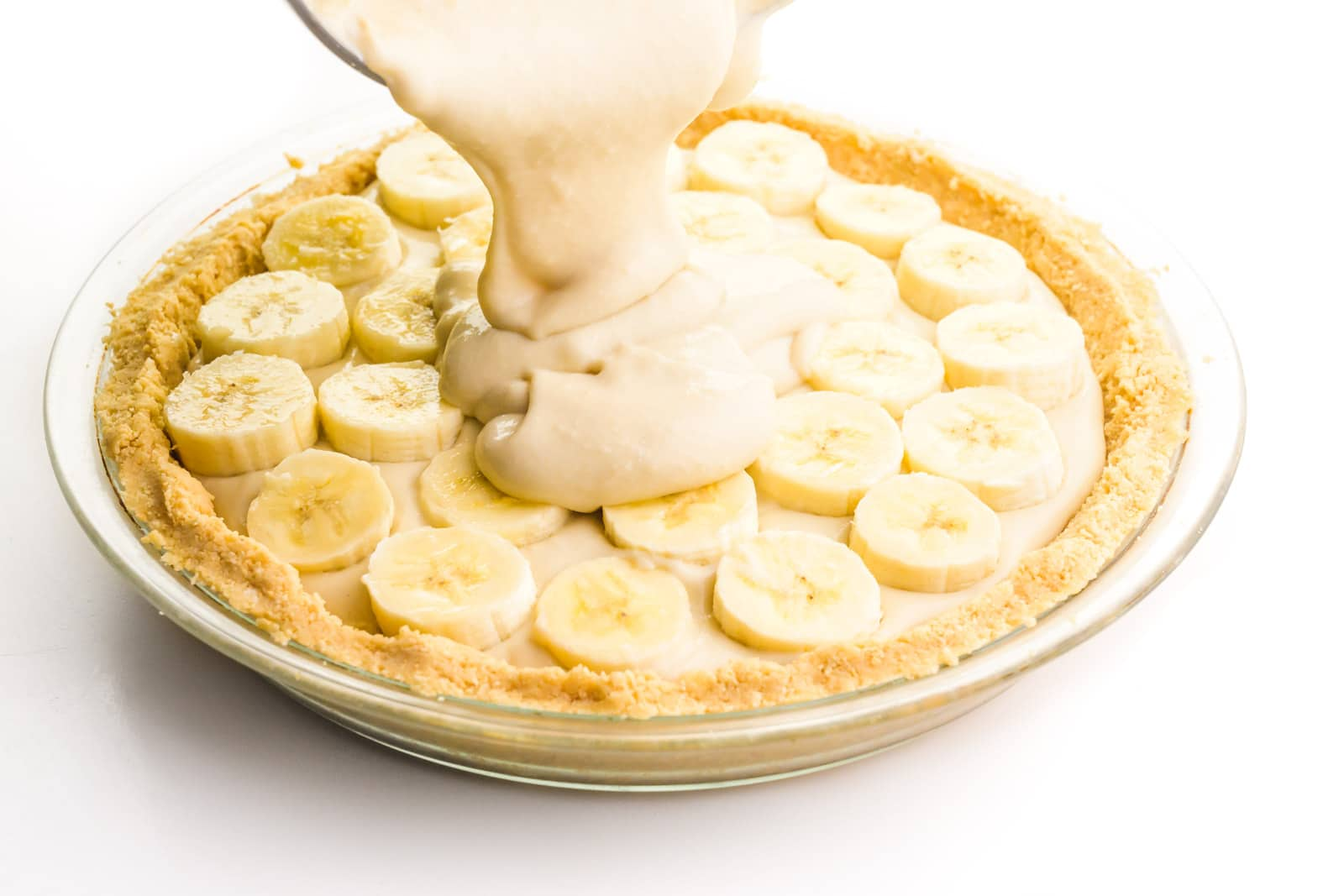 Vanilla pudding is being poured on top of a pie with pudding and banana slices on top.