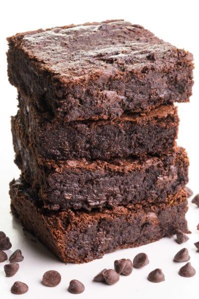 A stack of vegan black bean brownies has chocolate chips sitting around it.