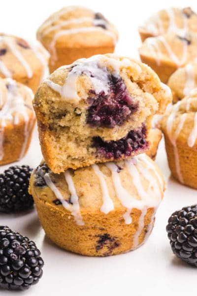 A blackberry muffin with a bite out of it sits on top of another muffin. There are fresh blackberries and more muffins around the stack.