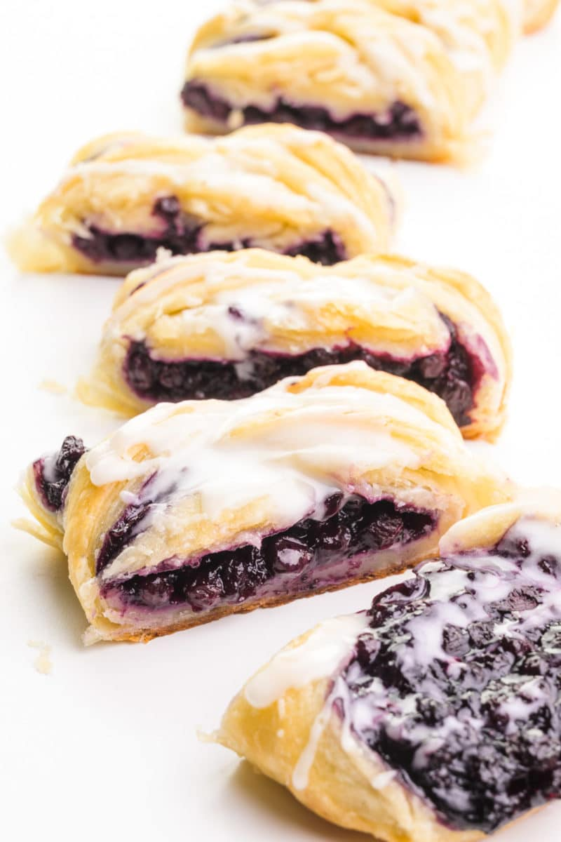 A vegan danish has been cut into pieces, showing lots of blueberry filling.