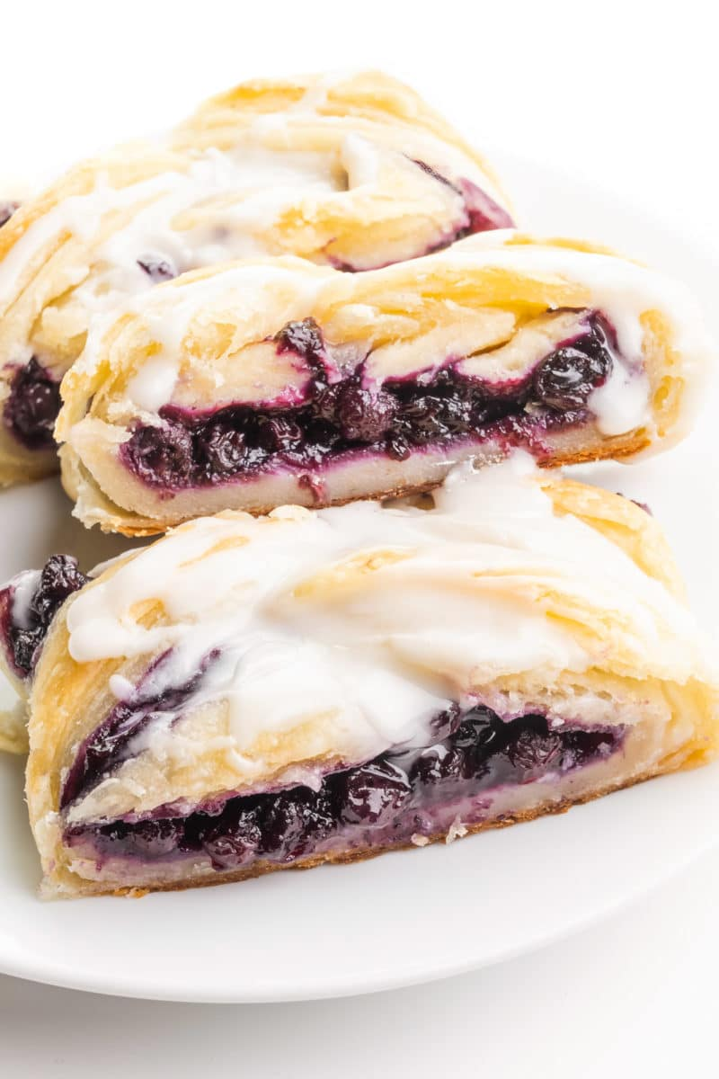 A vegan danish sits on a plate. It has blueberry filling and vanilla glaze on top.