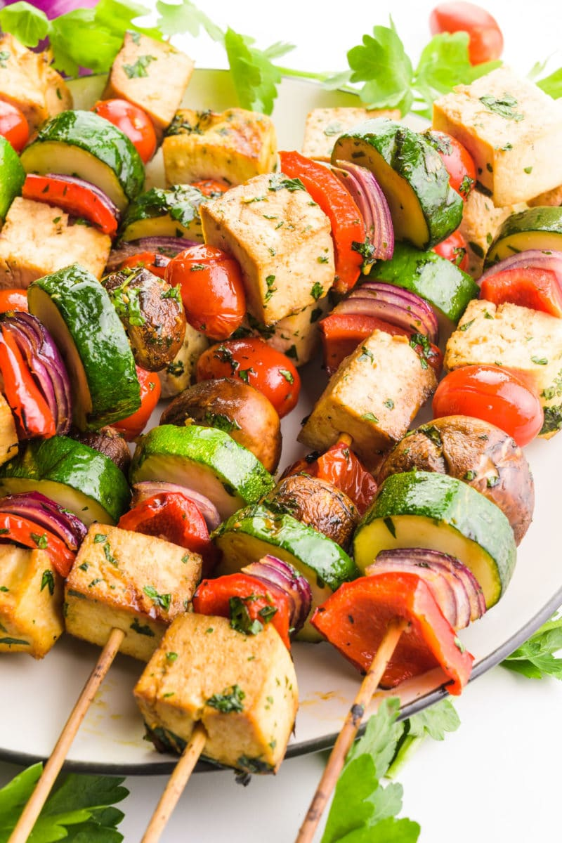 Cooked tofu skewers are on a plate. One skewer is placed diagonally across the others. There are pieces of fresh parsley and cherry tomatoes around the plate.