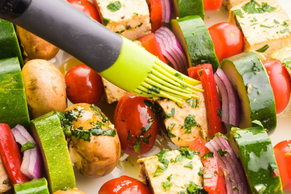 Vegan kebabs are being brushed with marinade before being placed on the grill.