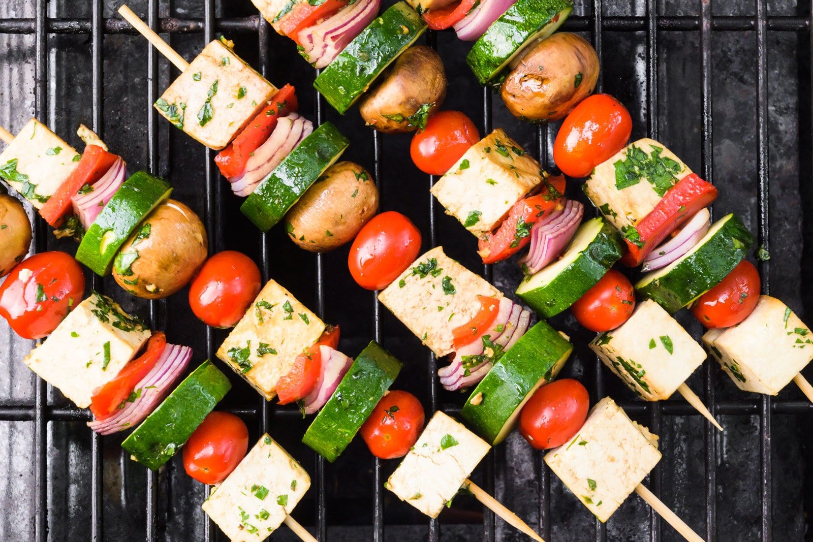 Looking down on vegan skewers on the grill. There are tofu cubes, sliced zucchini, cherry tomatoes, and more.