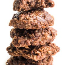 A stack of vegan no-bake cookies shows the top one with a bite taken out.