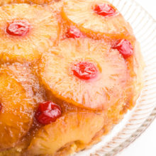 Looking down on a cake with pineapples and maraschino cherries on the outside.