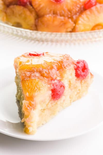 A slice of vegan pineapple upside down cake sits in front of the rest of the cake.