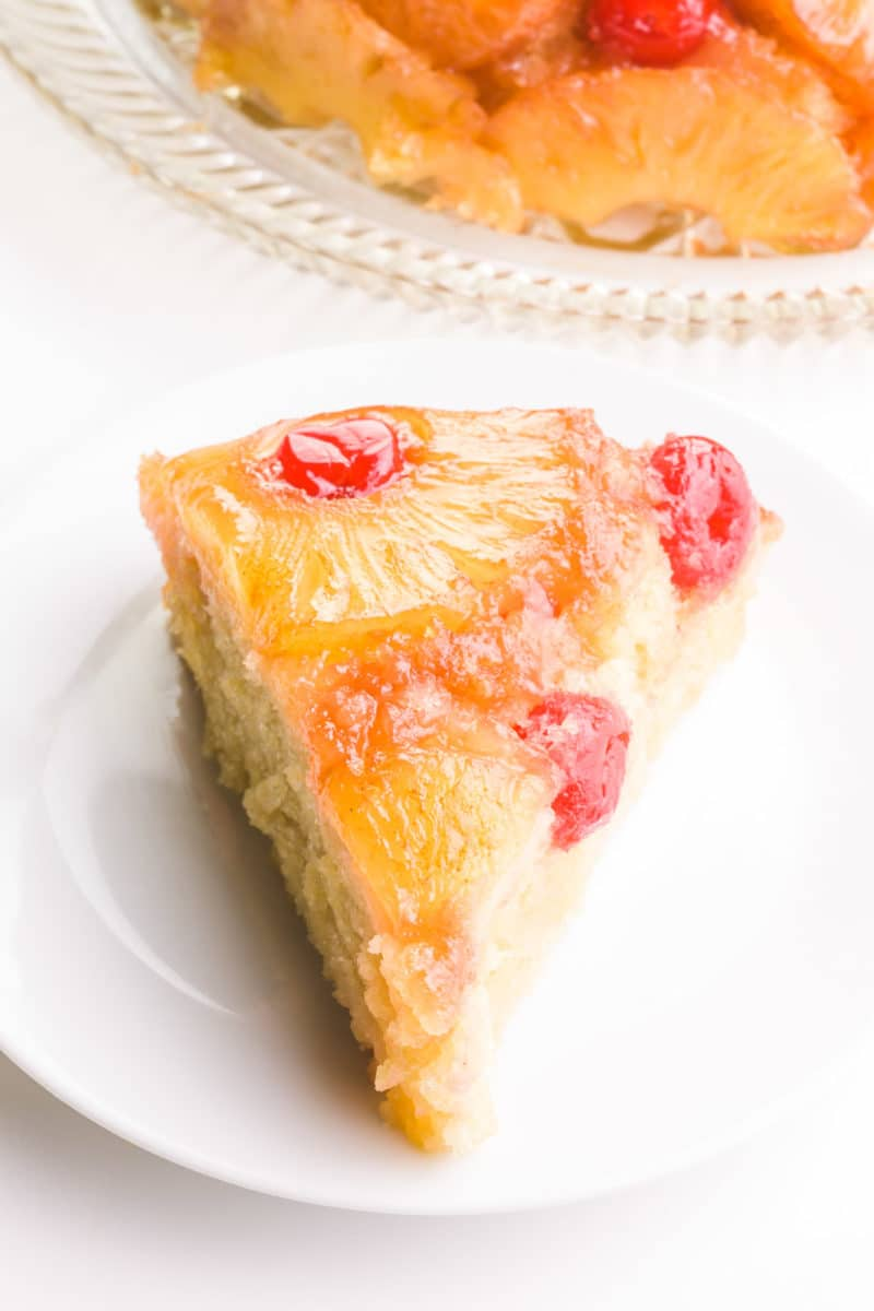 A slice of vegan pineapple upside down cake shows pineapples and maraschino cherries on top. The rest of the cake is behind it.