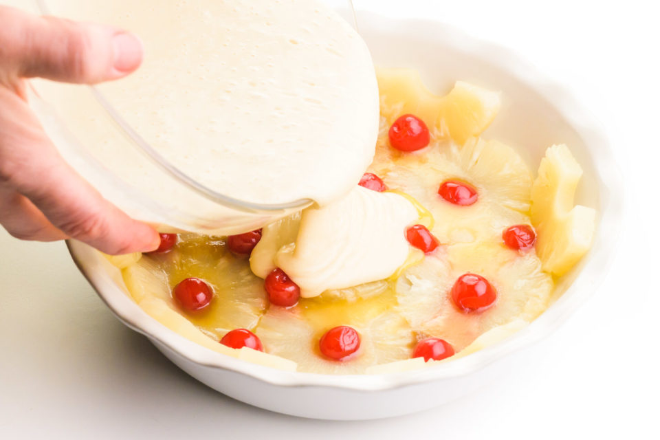 Cake batter is being poured over a pie pan lined with pineapple rings and cherries.