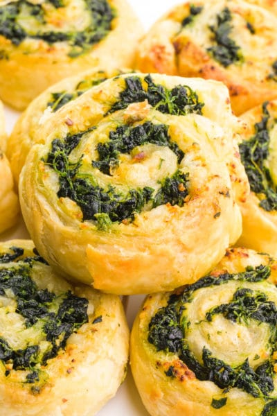 A spinach pinwheel sits on top several other pinwheels.