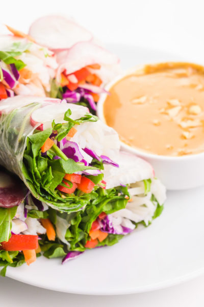 Vegan spring rolls are on a plate sitting next to peanut sauce.