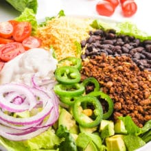 A vegan taco salad is topped with veggie taco meat, black beans, sliced jalapeños and more. There is more ingredients in the background, such as cherry tomatoes and lettuce.