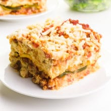 A serving of zucchini lasagna sits on a plate. There's another slice barely visible in the background.
